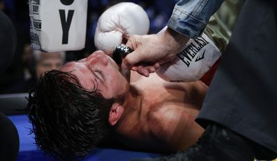 Trainer Joe Goossen removes a mouthguard from John Molina Jr. after his 11th-round knockout loss to Lucas Matthysse, of Argentina, in a junior welterweight boxing match Saturday, April 26, 2014, in Carson, Calif. (AP Photo/Jae C. Hong)