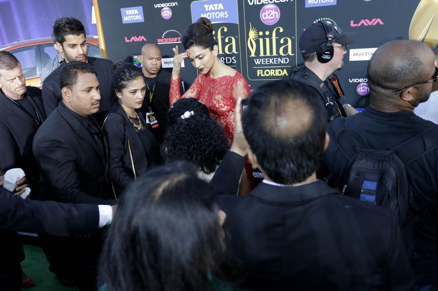 Deepika Padukone trys to figure out where to go on the red carpet outside Raymond James stadium for the 15th International Indian Film Academy Awards on Saturday, April 26, 2014 in Tampa,Fla. (AP Photo/Tampa Bay Times, James Borchuck)
