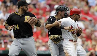 St. Louis Cardinals' Yadier Molina, right, is tagged out by Pittsburgh Pirates catcher Tony Sanchez, center, after being caught between third and home as Pirates third baseman Pedro Alvarez, left, watches during the second inning of a baseball game on Sunday, April 27, 2014, in St. Louis. (AP Photo/Jeff Roberson)