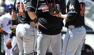 Miami Marlins pitching coach Chuck Hernandez talks with starting pitcher Tom Koehler (34) as catcher Jarrod Saltalamacchia (39) joins in after Koehler walked New York Mets Dillon Gee to load the bases in the second inning of a baseball game, Sunday, April 27, 2014, in New York. The Mets won 4-0. (AP Photo/Kathy Kmonicek)