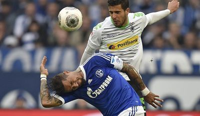 Moenchengladbach's Alvaro Dominguez of Spain, top, and Schalke's Kevin-Prince Boateng of Ghana challenge for the ball during the German Bundesliga soccer match between FC Schalke 04 and Borussia Moenchengladbach in Gelsenkirchen, Germany, Sunday, April 27, 2014. (AP Photo/Martin Meissner)
