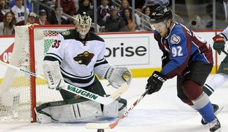 Colorado Avalanche left wing Gabriel Landeskog , right, of Sweden, tries to control the puck and shoot against Minnesota Wild goalie Darcy Kuemper, left, in the first period of Game 5 of an NHL hockey first-round playoff series on Saturday, April 26, 2014, in Denver.  (AP Photo/Chris Schneider)