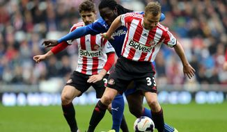 Cardiff City's Kenwyne Jones, center, vies for the ball with Sunderland's Fabio Borini, left, and Lee Cattermole, right, during their English Premier League soccer match at the Stadium of Light, Sunderland, England, Sunday, April 27, 2014. (AP Photo/Scott Heppell)