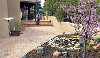 Santa Fe, New Mexico homeowner Hal Wingo, left, watches as Brian Tercero, of Keller Williams Realty flies his  DJI Phantom drone as he takes video of the garden on April 18, 2014, in Santa Fe, N.M.  (AP Photo/The Santa Fe New Mexican,  Clyde Mueller)