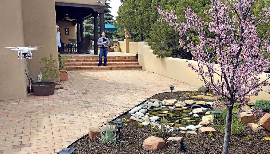 Santa Fe, New Mexico homeowner Hal Wingo, left, watches as Brian Tercero, of Keller Williams Realty flies his  DJI Phantom drone as he takes video of the garden on April 18, 2014, in Santa Fe, N.M.  (AP Photo/The Santa Fe New Mexican,  Clyde Mueller)