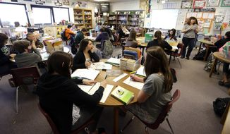In this April 18, 2014 photo, Annette Wells, right, leads a discussion in her 7th-8th grade language arts class at Komachin Middle School in Lacey, Wash. (AP Photo/Ted S. Warren) ** FILE **