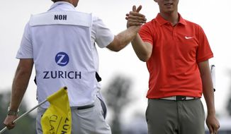 Noh Seung-yul, right, of South Korea, is congratulated by caddy Scott Sajtinac on the 18th green after winning the Zurich Classic golf tournament at TPC Louisiana in Avondale, La., Sunday, April 27, 2014. (AP Photo/Bill Haber)