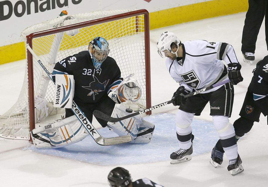 San Jose Sharks goalie Alex Stalock (32) blocks a goal attempt by Los Angeles Kings right wing Justin Williams (14) during the third period of Game 4 of an NHL hockey first-round playoff series in San Jose, Calif., Saturday, April 26, 2014. Los Angeles won 3-0.  (AP Photo/Tony Avelar)