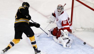 Boston Bruins' Milan Lucic (17) scores past Detroit Red Wings' Jonas Gustavsson (50) during the third period in Game 5 in the first round of the NHL hockey Stanley Cup playoffs  in Boston, Saturday, April 26, 2014. (AP Photo/Michael Dwyer)