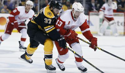 Boston Bruins' Patrice Bergeron (37) and Detroit Red Wings' Pavel Datsyuk (13) battle for the puck during the first period in Game 5 in the first round of the NHL hockey Stanley Cup playoffs  in Boston, Saturday, April 26, 2014. (AP Photo/Michael Dwyer)