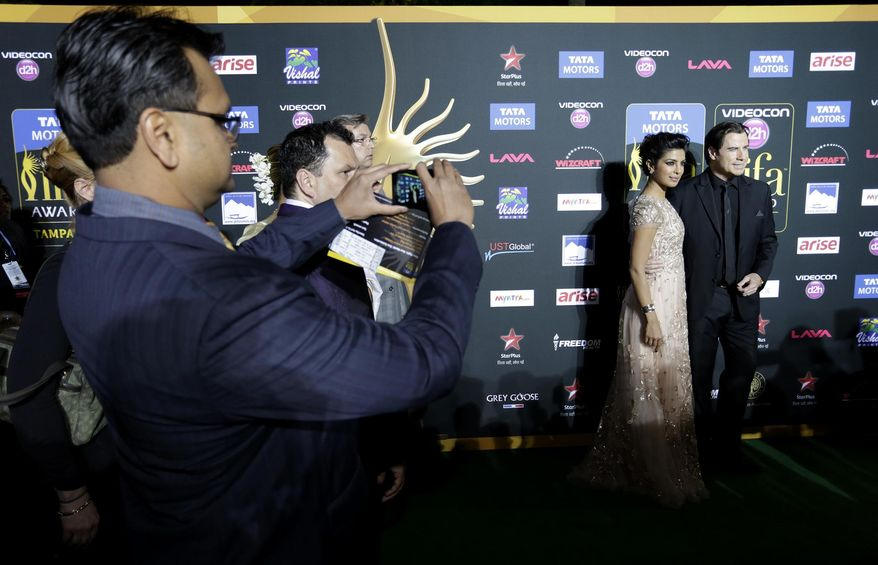 Priyanka Chopra poses for pictures with John Travolta on the Green Carpet in front of Raymond James stadium for the 15th International Indian Film Academy Awards on Saturday, April 26, 2014 in Tampa,Fla. (AP Photo/Tampa Bay Times, James Borchuck)