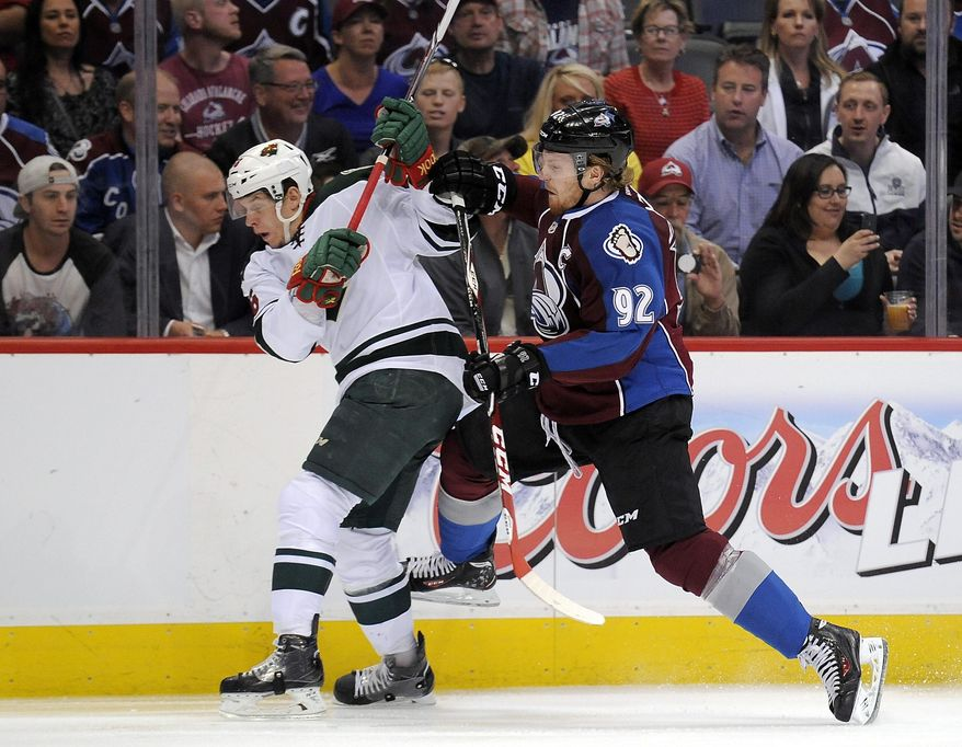 Colorado Avalanche left wing Gabriel Landeskog, right, of Sweden, checks Minnesota Wild left wing Erik Haula, left, of Finland, in the first period of Game 5 of an NHL hockey first-round playoff series on Saturday, April 26, 2014, in Denver.  (AP Photo/Chris Schneider)