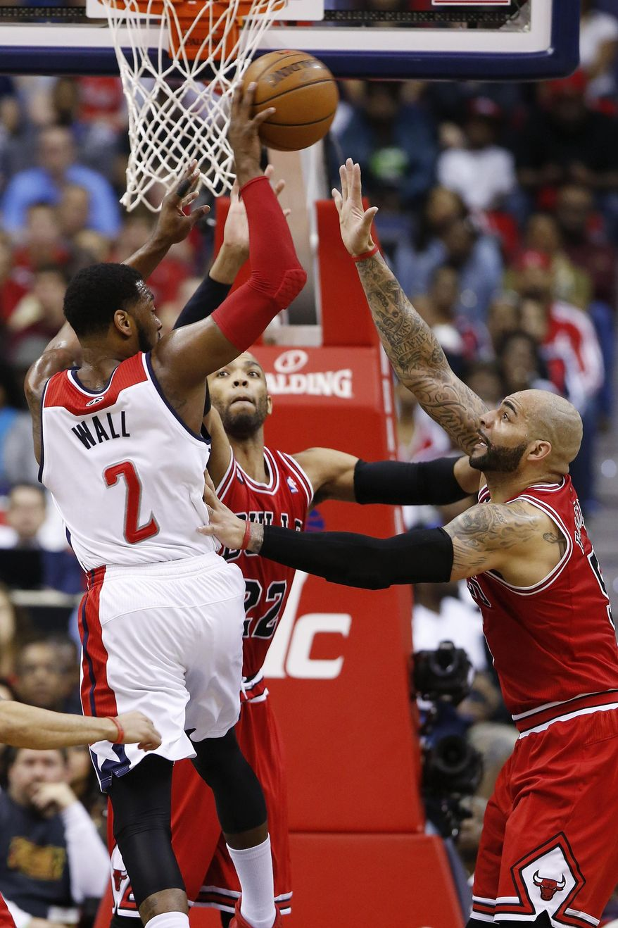 Washington Wizards guard John Wall (2) passes over Chicago Bulls forward Taj Gibson (22) and forward Carlos Boozer (5) during the first half of Game 4 of an opening-round NBA basketball playoff series in Washington, Sunday, April 27, 2014. (AP Photo/Alex Brandon)