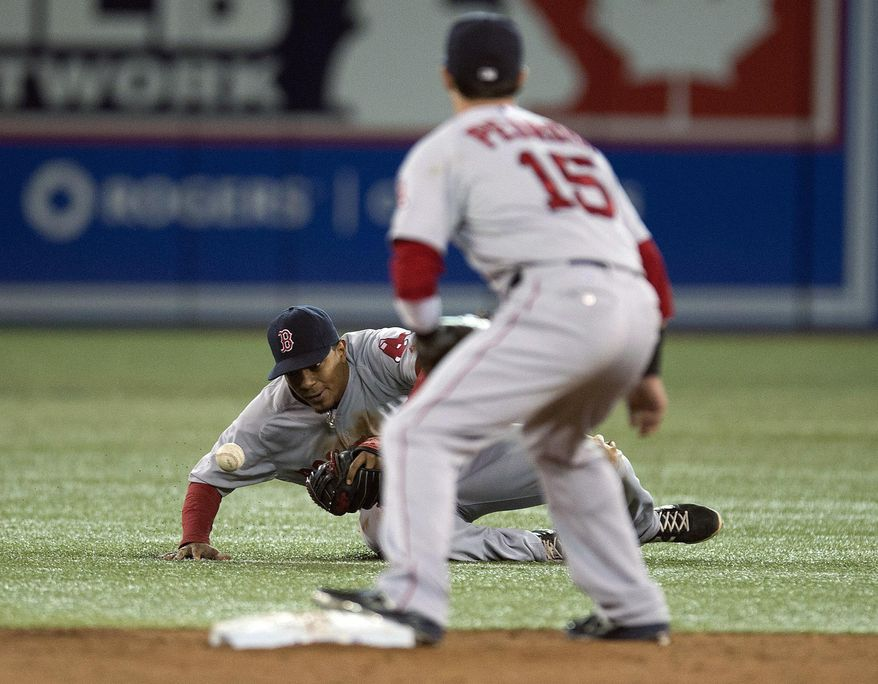 Boston Red Sox's Xander Bogaerts tries to field a groundball on an infield single from Toronto Blue Jays' Jose Bautista as Dustin Pedroia (15) looks on during eighth inning of a baseball game against in Toronto on Sunday, April 27, 2014. (AP Photo/The Canadian Press, Frank Gunn)