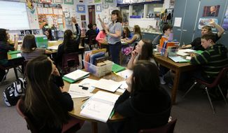 **FILE** In this April 18, 2014, photo, Annette Wells, center, takes questions in her seventh-eighth grade language arts class at Komachin Middle School in Lacey, Wash. (AP Photo/Ted S. Warren)