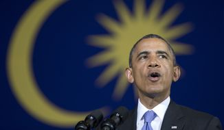 With a Malaysian flag behind him, President Barack Obama speaks during a town hall meeting at Malaya University in Kuala Lumpur, Malaysia, Sunday, April 27, 2014. (AP Photo/Carolyn Kaster)
