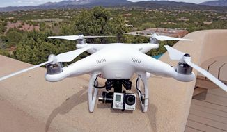 The remote controlled DJI Phantom drone with an attached GoPro 3 camera used by Brian Tercero of Keller Williams Realty used to create a high definition video of a property is seen in Santa Fe, N.M. on April 18, 2014. (AP Photo/The Santa Fe New Mexican, Clyde Mueller)