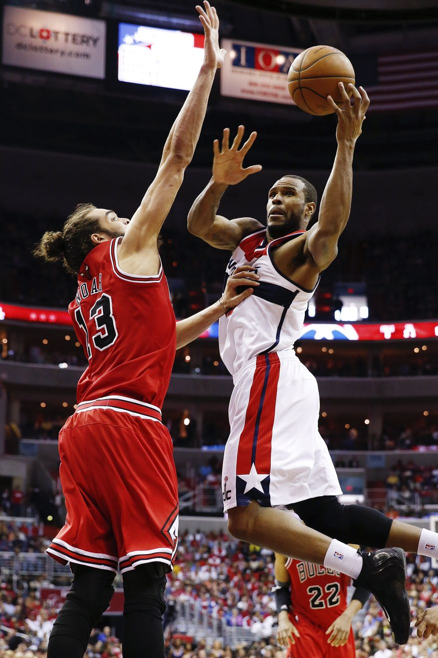Washington Wizards forward Trevor Booker, right, shoots over Chicago Bulls center Joakim Noah (13) during the second half of Game 4 of an opening-round NBA basketball playoff series in Washington, Sunday, April 27, 2014. The Wizards defeated the Bulls 98-89. (AP Photo/Alex Brandon)