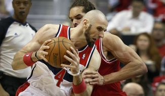Washington Wizards center Marcin Gortat (4), from Poland, drives past Chicago Bulls center Joakim Noah during the first half of Game 4 of an opening-round NBA basketball playoff series in Washington, Sunday, April 27, 2014. (AP Photo/Alex Brandon)