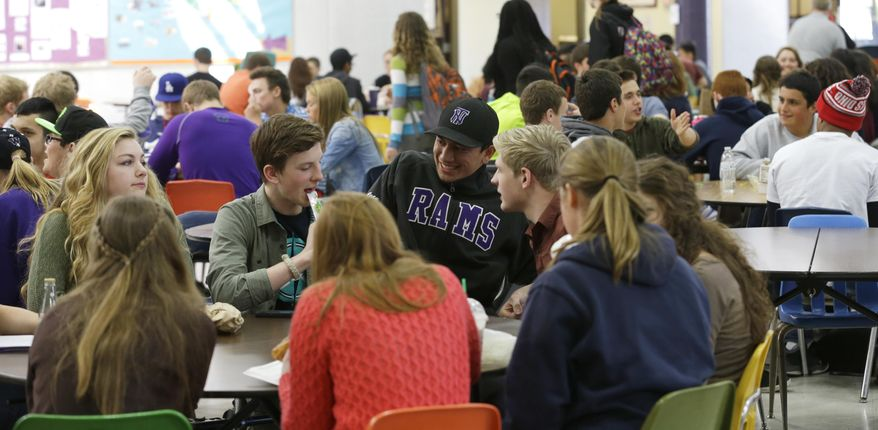 In this April 18, 2014 photo, students at North Thurston High School in Olympia, Wash. fill nearly every available seat during a lunch period, which has 700 students scheduled but only seating for 240. An Associated Press analysis of Washington school enrollment data shows 136 school districts, out of 295, added students between the 2011-12 school year and the current academic year. (AP Photo/Ted S. Warren)