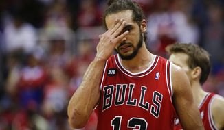 Chicago Bulls center Joakim Noah (13) holds his hand to his head during a break in the action against the Washington Wizards during the first half of Game 4 of an opening-round NBA basketball playoff series in Washington, Sunday, April 27, 2014. (AP Photo/Alex Brandon)