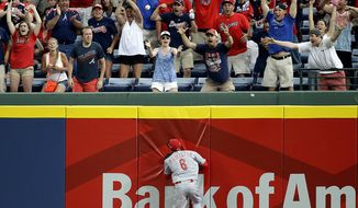 Fans celebrate as Cincinnati Reds' Billy Hamilton chases down a single by Atlanta Braves' Freddie Freeman to score the game-winning run in the 10th inning of a baseball game, Sunday, April 27, 2014, in Atlanta. The Braves won 1-0 in 10 innings. (AP Photo/David Goldman)