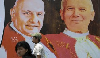 Two persons walk in front of pictures of Pope John XXIII, left, and Pope John Paul II in Guatemala City, Sunday, April 27, 2014. The canonization of Pope John Paul II and Pope John XXIII is drawing special attention in Latin America, reviving both warm memories of his frequent visits to the region and debate over his handling of sex-abuse scandals. (AP Photo/Luis Soto)