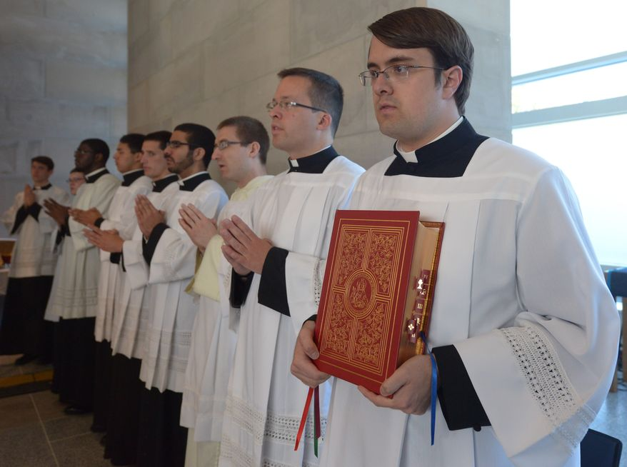 Seminary Michael Russo holds the Holy Bible during the Mass of Thanksgiving on Sunday, April 27 at the Saint John Paul II National Shrine. Khalid Naji-Allah Special to The Washington Times