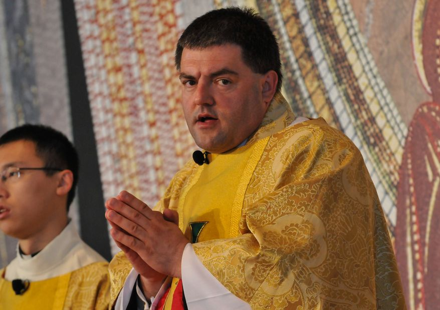 Father Gregory Gresko, Chaplain of the Saint John Paul II National Shrine, sings a hymn during the Mass of Thanksgiving on Sunday, April 27 at the Saint John Paul II National Shrine. Khalid Naji-Allah Special to The Washington Times