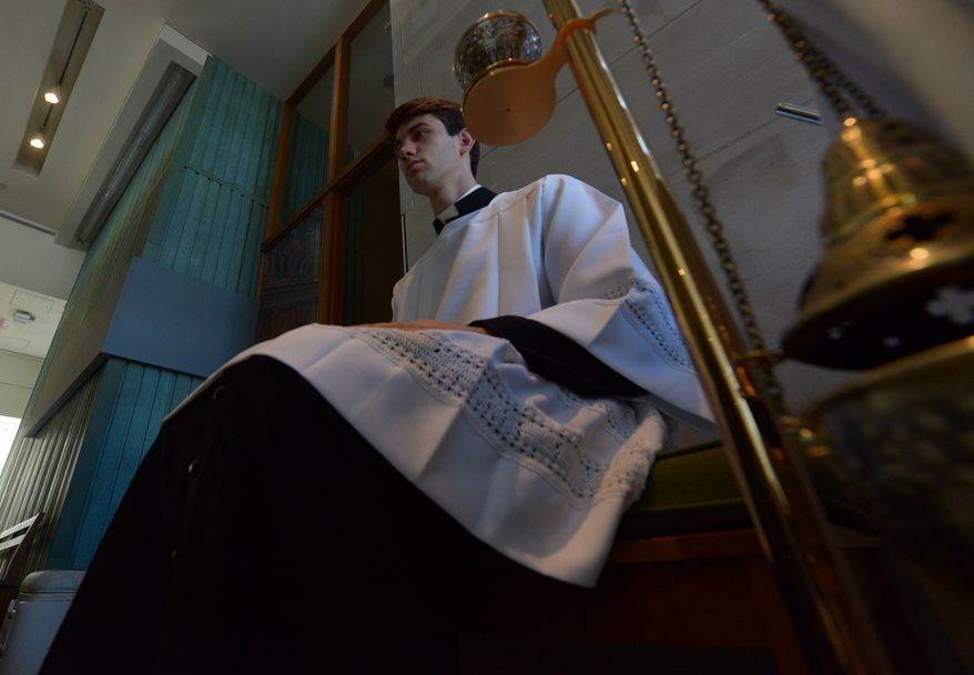 Seminary Kevin Kayser, 20, right, sits with the thurible in the back of the altar during the Mass of Thanksgiving on Sunday, April 27 at the Saint John Paul II National Shrine. Khalid Naji-Allah Special to The Washington Times