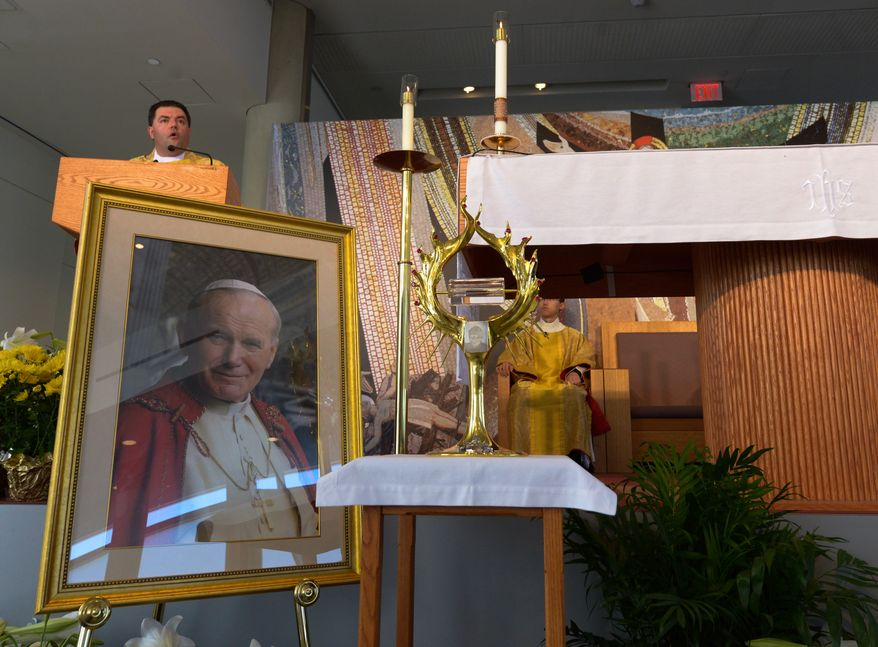 Father Gregory Gresko, Chaplain of the Saint John Paul II National Shrine, delivers his homily overlooking a portrait of Pope John Paul II and the relic containing the blood of the former Pontiff during the Mass of Thanksgiving on Sunday, April 27 at the Saint John Paul II National Shrine. Khalid Naji-Allah Special to The Washington Times