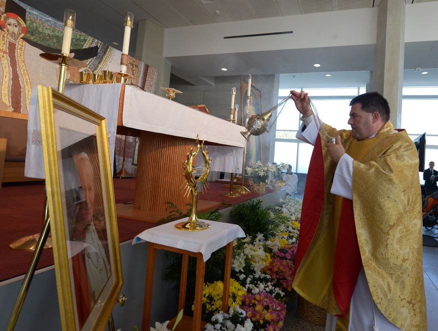 Father Gregory Gresko, Chaplain of the Saint John Paul II National Shrine, blesses the altar area during the Mass of Thanksgiving on Sunday, April 27 at the Saint John Paul II National Shrine. Khalid Naji-Allah Special to The Washington Times