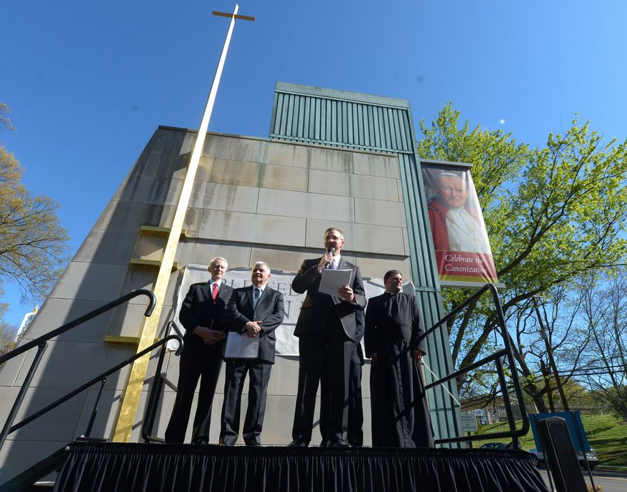 Patrick Kelly, Executive Director of the Pope John Paul II National Shrine, center, along with members of the Knights of Columbus offer remarks during the unveiling ceremony of the renamed shrine dedicated to Pope John Paul II to reflect the sainthood bestowed upon him on Sunday, April 27 in Northeast. Khalid Naji-Allah Special to The Washington Times