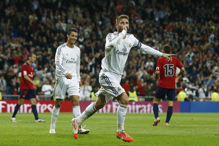 Real's Sergio Ramos, center, celebrates his goal during a Spanish La Liga soccer match between Real Madrid and Osasuna at the Santiago Bernabeu stadium in Madrid, Spain, Saturday, April 26, 2014. (AP Photo/Andres Kudacki)