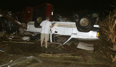 John Ward, an automobile and RV dealer, looks at tornado damage to one of his trucks in Mayflower, Ark., Sunday, April 27, 2014. At least 16 people died Sunday night in Arkansas as a tornado carved an 80-mile path of destruction. (AP Photo/Danny Johnston)
