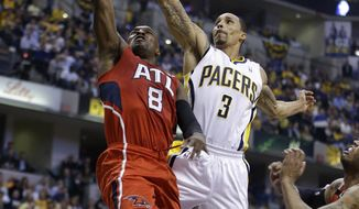 Atlanta Hawks' Shelvin Mack (8) puts up a shot against Indiana Pacers' George Hill (3) during the first half in Game 5 of an opening-round NBA basketball playoff series Monday, April 28, 2014, in Indianapolis. (AP Photo/Darron Cummings)