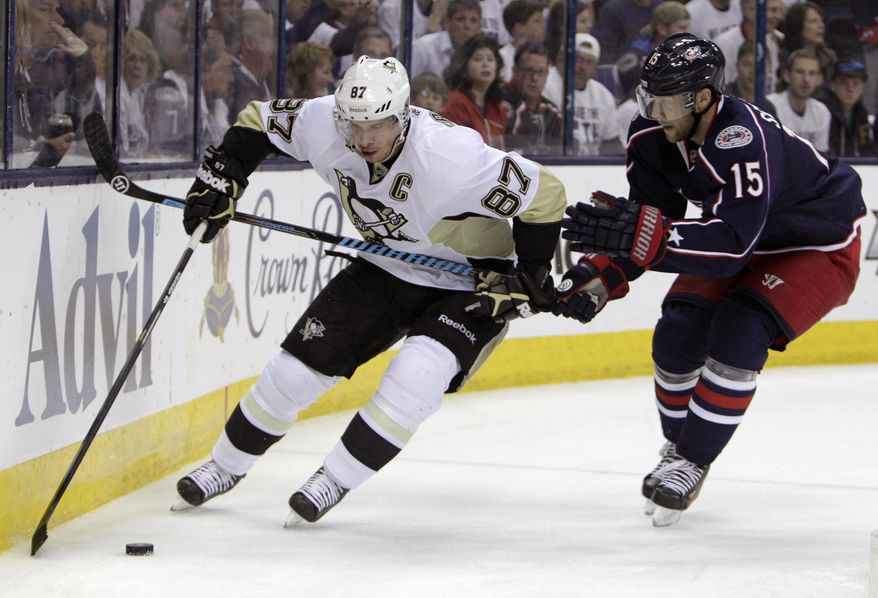 Pittsburgh Penguins' Sidney Crosby, left, tries to carry the puck past Columbus Blue Jackets' Nick Shultz during the first period of Game 6 of a first-round NHL playoff hockey series Monday, April 28, 2014, in Columbus, Ohio. (AP Photo/Jay LaPrete)