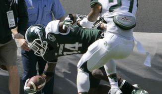 Green team receiver Tony Lippett (14) is pushed out of bounds by White team's Kurtis Drummond (27) during Michigan State's NCAA college spring football scrimmage on Saturday, April 26, 2014, in East Lansing, Mich. The White team won 20-13. (AP Photo/Al Goldis)