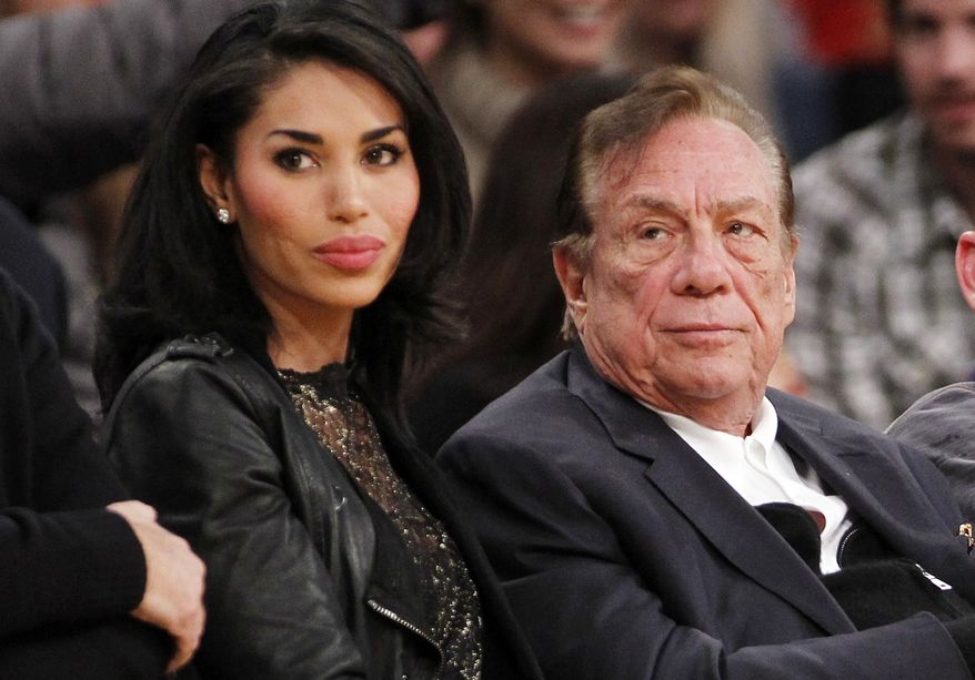 Los Angeles Clippers owner Donald Sterling and V. Stiviano watch an NBA preseason game in 2010. (AP Photo/Danny Moloshok, File)
