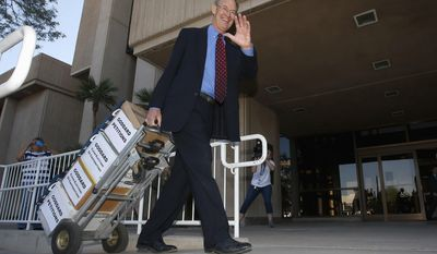 Former Arizona Attorney General Terry Goddard, smiles and waves to cameras as he arrives at the Arizona Capitol to file his nominating petitions to run as a Democrat in the race for secretary of state on Monday, April 28, 2014, in Phoenix.  Goddard pulls four boxes on a hand truck with his 9,000 qualifying signatures and more than 3,300 $5 contributions for verification that will qualify him for public funding under the state's clean elections law. (AP Photo/Ross D. Franklin)