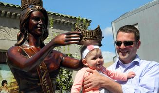Mike Van Gorden of Brick N.J. holds his 8-month-old daughter Luciana underneath the crown of the Miss America statue moments before it was dedicated in a ceremony on the Atlantic City N.J. Boardwalk on Monday, April 28, 2014. Van Gorden was part of the team that designed and built the statue, designed to be a year-round tourist attraction. (AP Photo/Wayne Parry)