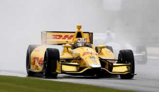 Ryan Hunter-Reay kicks up cloud water spay as he leads a pack of cars down the backstrech during the Indy Grand Prix of Alabama on Sunday, April 27, 2014, in Birmingham, Ala. (AP Photo/Butch Dill)