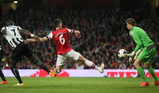 Arsenal's Laurent Koscielny, kicks the ball past Newcastle's goalkeeper Tim Krul to score the opening goal during, their English Premier League soccer match between Arsenal and Newcastle United at the Emirates stadium in London, Monday, April 28,  2014. (AP Photo/Alastair Grant)