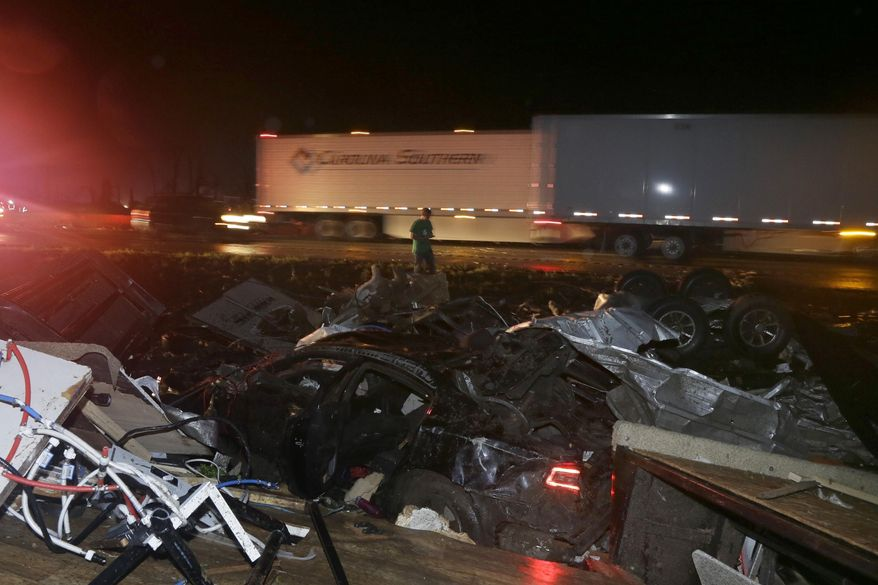 A man walks past a wrecked automobile and RV on Interstate 40 in Mayflower, Ark., Sunday, April 27, 2014. A powerful storm system rumbled through the central and southern United States on Sunday, spawning a massive tornado (AP Photo/Danny Johnston)