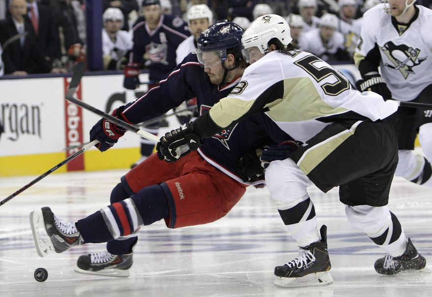 Pittsburgh Penguins' Kris Letang, right, knocks Columbus Blue Jackets' Boone Jenner off of the puck during the second period of Game 6 of a first-round NHL playoff hockey series Monday, April 28, 2014, in Columbus, Ohio. (AP Photo/Jay LaPrete)