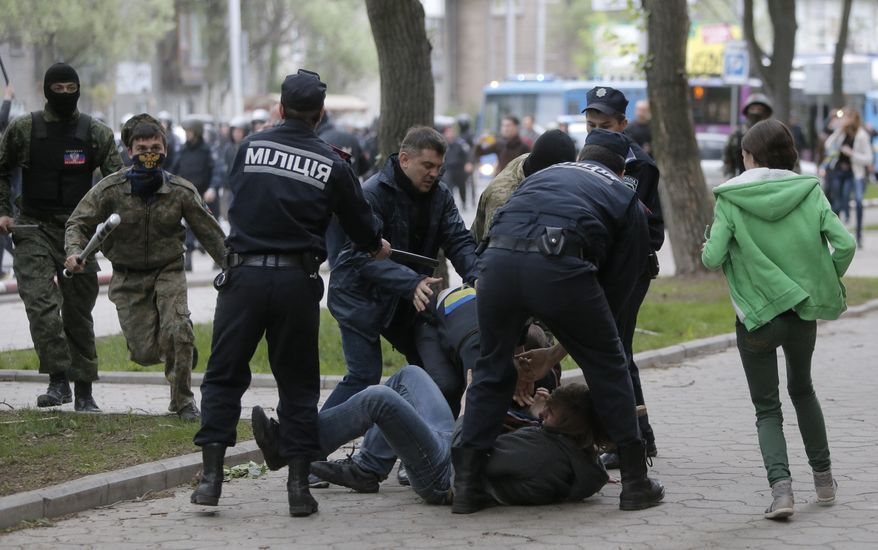 Masked pro-Russian activists beat a participant of a pro-Ukrainian rally as police try to stop the clash in Donetsk, Ukraine, Monday, April 28, 2014. About a thousand pro-Russian activists armed with sticks and steel rods attacked the participants of pro-Ukrainian rally in center of Donetsk. (AP Photo/Efrem Lukatsky)