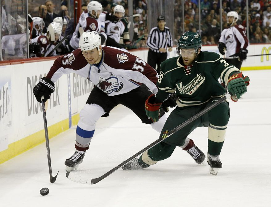 Colorado Avalanche left wing Cody McLeod (55) and Minnesota Wild defenseman Nate Prosser (39) chase the puck during the second period of Game 6 of an NHL hockey first-round playoff series in St. Paul, Minn., Monday, April 28, 2014. (AP Photo/Ann Heisenfelt)