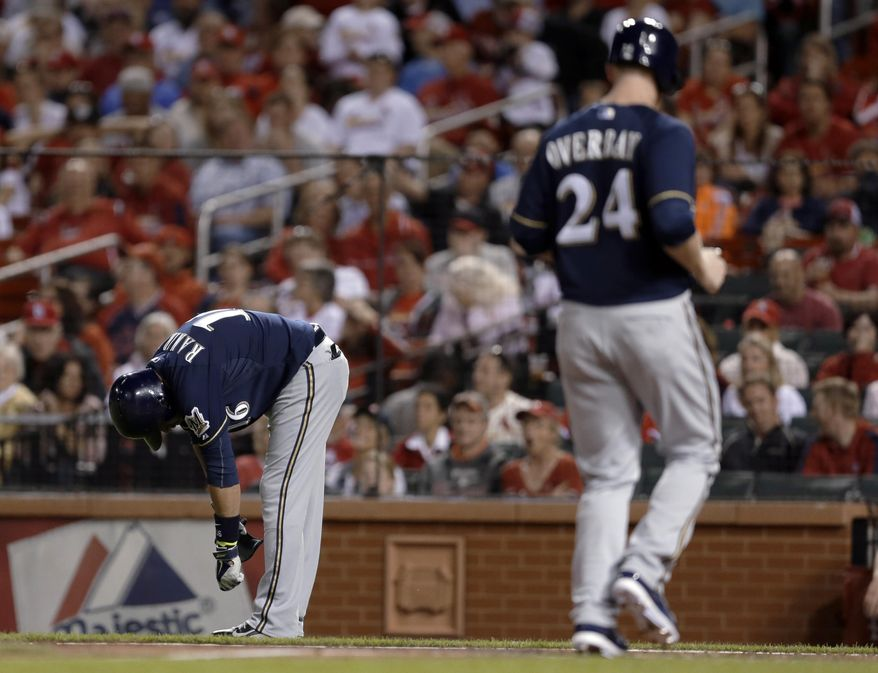 Milwaukee Brewers' Lyle Overbay, right, jogs in to score the tying run after Aramis Ramirez, left, was hit by a pitch with the bases loaded during the seventh inning of a baseball game against the St. Louis Cardinals on Monday, April 28, 2014, in St. Louis. (AP Photo/Jeff Roberson)