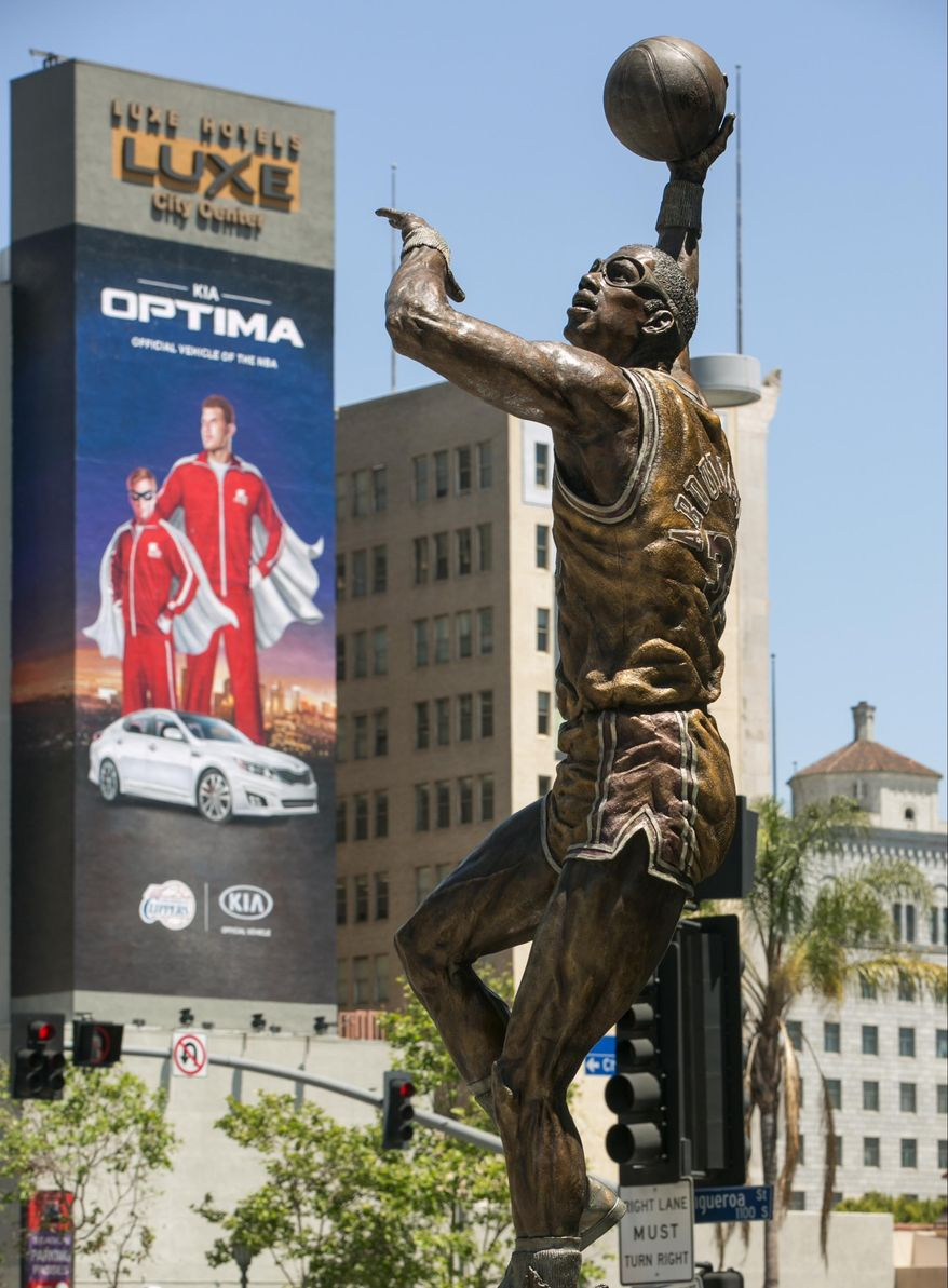 A statue of NBA great Kareem Abdul-Jabbar stands outside Staples Center in Los Angeles on Tuesday, April 29, 2014. Kia Motors America, whose ad on a building near the arena features Clippers forward Blake Griffin, said it is suspending advertising and sponsorship activities with the Clippers. The Clippers and the Golden State Warriors are to play Game 5 of a first-round playoff series later Tuesday. (AP Photo)
