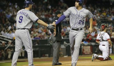 Colorado Rockies' Nolan Arenado (28) greets teammate D.J. LeMahieu (9) after scoing on an RBI by teammate Jordan Pacheco against the Arizona Diamondbacks during the fourth inning of a baseball game on Monday, April 28, 2014, in Phoenix. (AP Photo/Matt York)